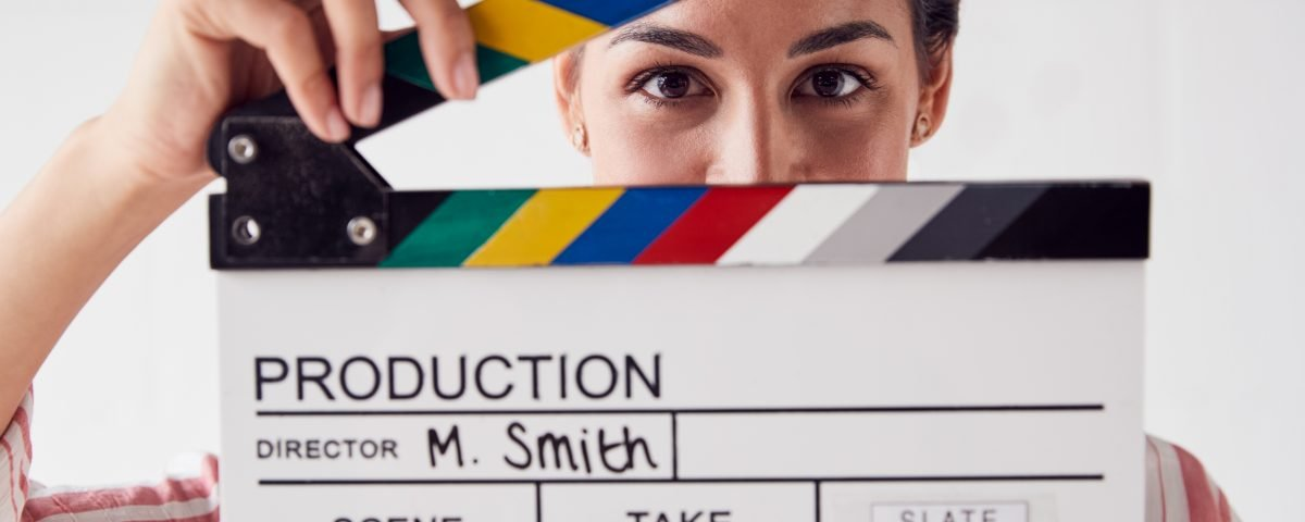 Portrait Of Female Videographer Holding Clapper Board On Video Film Production In White Studio